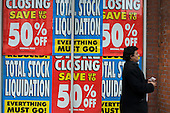 Store Closing and Total Stock Liquidation posters in the windows of a Woolworths store in North London
