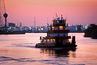 A tugboat, lit up at sunset as it travels in the Houston Ship channel. Houston, Texas.