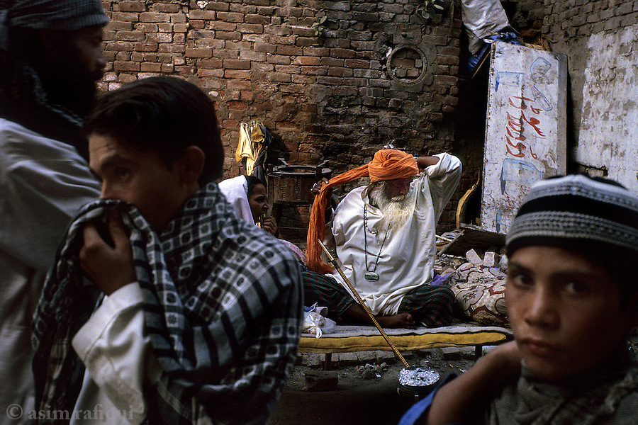 Street scene in the alleys of the old city of lahore in pakistan - men gather around an elder to seek advice