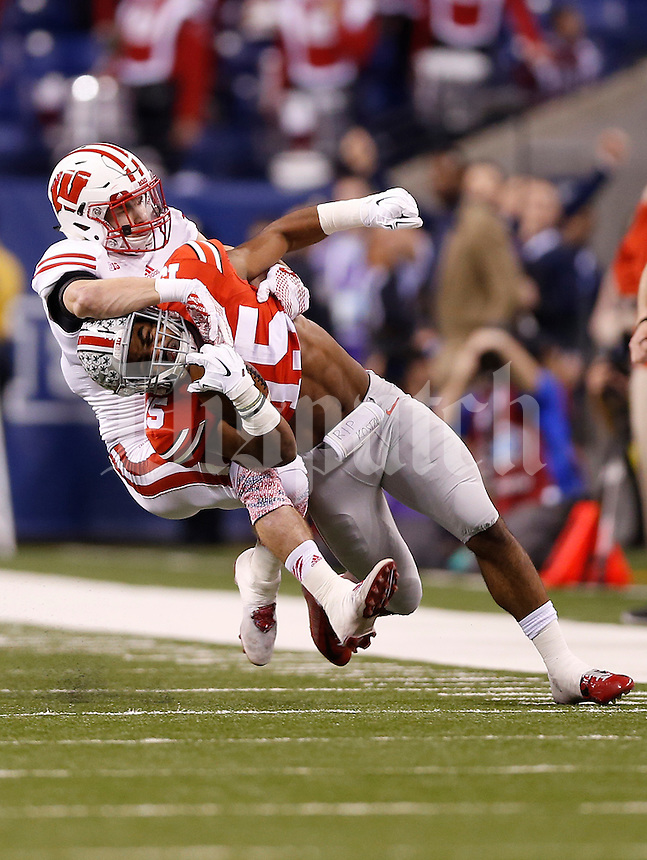 Ohio State Buckeyes running back Ezekiel Elliott (15) gets taken down by Wisconsin Badgers safety Michael Caputo (7) in the first quarter of the Big Ten Championship game between the Ohio State Buckeyes and the Wisconsin Badgers at Lucas Oil Stadium in Indianapolis, Saturday night, December 6, 2014. As of half time the Ohio State Buckeyes led the Wisconsin Badgers 38 - 0. (The Columbus Dispatch / Eamon Queeney)