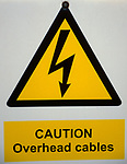 A87CJB Yellow caution overhead cables sign warning of the risk of electrocution