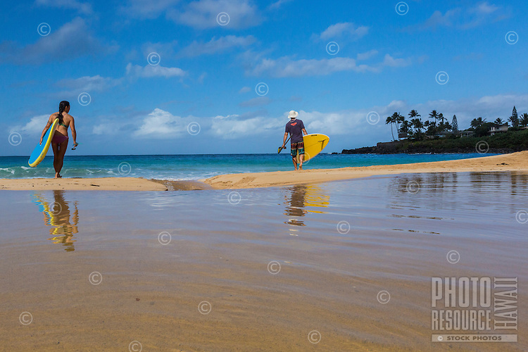 After standup paddling in Waimea River, a woman and man take their boards into Waimea Bay at Waimea Beach Park, O'ahu.