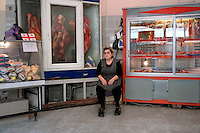 A woman sits in a butcher's shop in Tbilisi....