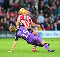 Lincoln City's Matt Rhead vies for possession with  Port Vale's Nathan Smith<br /> <br /> Photographer Andrew Vaughan/CameraSport<br /> <br /> The EFL Sky Bet League Two - Lincoln City v Port Vale - Tuesday 1st January 2019 - Sincil Bank - Lincoln<br /> <br /> World Copyright &copy; 2019 CameraSport. All rights reserved. 43 Linden Ave. Countesthorpe. Leicester. England. LE8 5PG - Tel: +44 (0) 116 277 4147 - admin@camerasport.com - www.camerasport.com