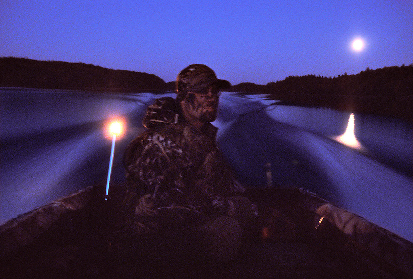 A WATERFOWL HUNTER MOTORS ACROSS A LAKE UNDER A FULL MOON NEAR ISHPEMING, MICHIGAN.