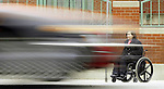 NOT MODEL RELEASED; FOR EDITORIAL USE ONLY... woman in wheelchair waiting in sidewalk for public transportation bus as traffic whizzes by