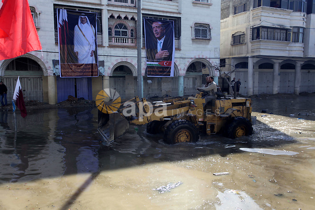 A Palestinian man works on a bulldozer at Al Sheikh Redwan area that was flooded in Gaza City, 18 December 2013. Four days of torrential rains in Gaza Strip killed two people and forced the evacuation of more than 5,000 residents from flooded homes, some accessible only by boat, officials said. Photo by Ashraf Amra