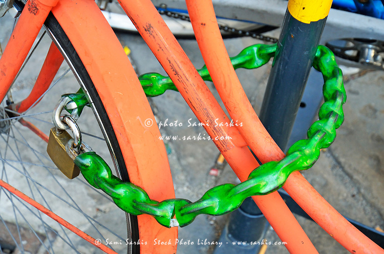 Locker and green chain on orange bicycle, Florence, Italy