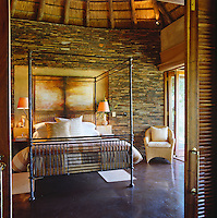 An iron-framed four-poster bed in a contemporary bedroom with a curved wall of shale