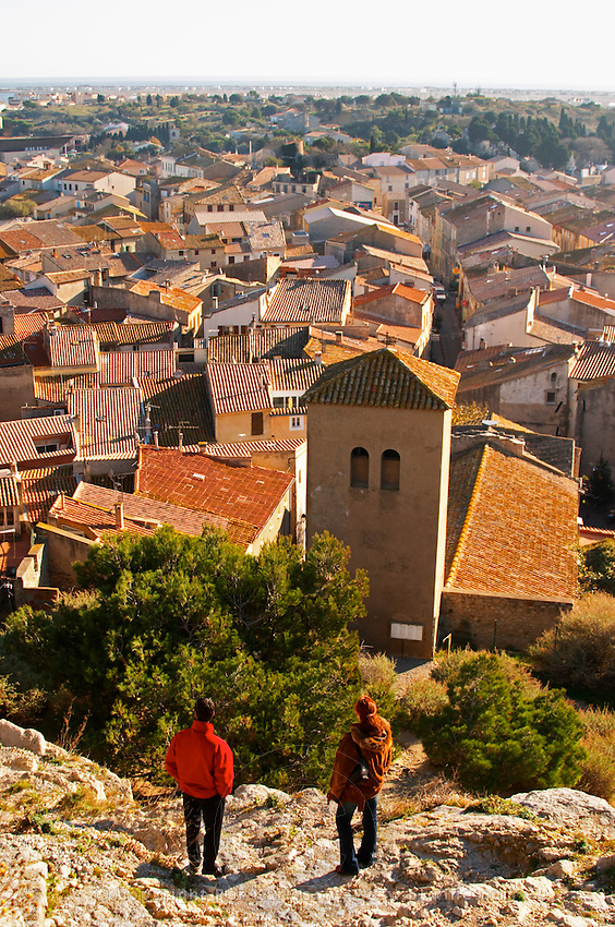 Gruissan village. La Clape. Languedoc. Village roof tops with tiles. A tourist couple admiring the view. France. Europe.