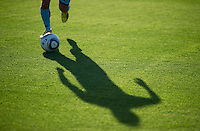 Soccer player shadow runnng with ball.