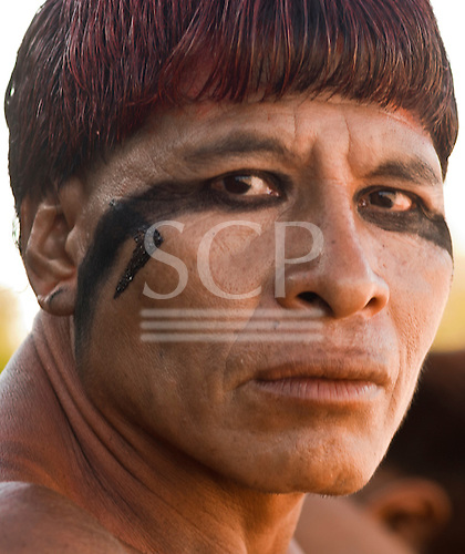 Xingu Indigenous Park, Mato Grosso State, Brazil. Aldeia Waura. Warrior Yapatchama Waura in war paint looking angry against the building of the dam.