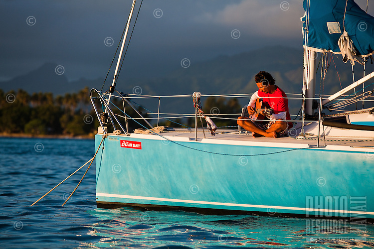 Man playing guitar on yacht at sunrise in lagoon off Tahaa Island