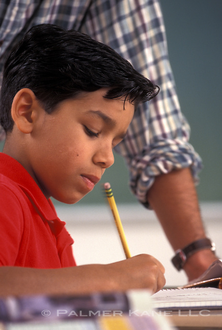 Latino student working in class under teacher supervision