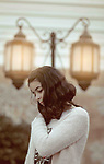 A pretty girl puts one hand at her shoulder with lamps at background. Photo by Sanad Ltefa