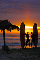 Long Board Surfers At Sunset