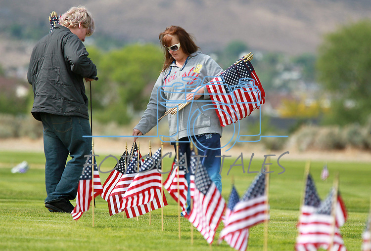 Travis Phalin, 16, and his mom Jeanie place flags on the graves of veterans at the Lone Mountain Cemetery in Carson City, Nev., on Friday, May 25, 2012. Volunteers from the D.A.V., American Legion, Carson High School ROTC and Boy Scout Troop 145 placed more than 1,400 flags on the graves of veterans in honor of Memorial Day..Photo by Cathleen Allison