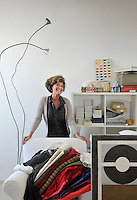 The designer of the house, Marina Sinibaldi, in her studio surrounded by swatches of fabric