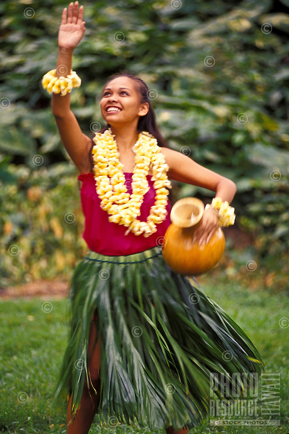 Young woman dancing hula with ipu (gourd) and plumeria leis in ti leaf skirt