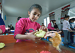 "A girl creates clothing for Barbie with modeling clay in a church-sponsored ""child-friendly space"" in the village of Bakhtme, Iraq, which was flooded with displaced families when the Islamic State group took over nearby portions of the Nineveh Plains in 2014. The space is sponsored by the Christian Aid Program Nohadra - Iraq (CAPNI). It includes some children from the host community as well."