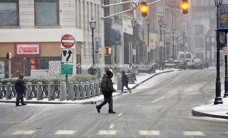 WATERBURY, CT - 10 FEBRUARY 2010 -021010JT03--<br /> Several pedestrians walk along and across Bank Street near the Waterbury Green on Wednesday afternoon during a snow storm that was forecasted to drop four to eight inches of snow throughout the area.<br /> Josalee Thrift Republican-American