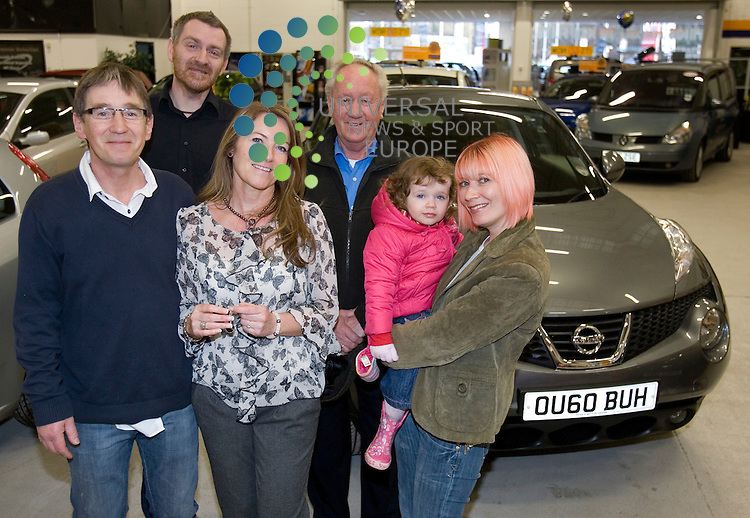 Competition winner Anne Hutton (Middle front) with partner Thomas Johnstone and with other family members Susan Johnstone and Molly, Colin Htton (Tall) with father of Anne William Hutton (white Hair) and her new Nissan Juke at the East kilbride Dealership..Picture:Universal News And Sport (Scotland) .11 December 2010...