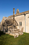 Building exterior church of Saint John, Inglesham, Wiltshire, England, UK stone construction dating back to13th century with three stepped 15th century churchyard cross cross in graveyard