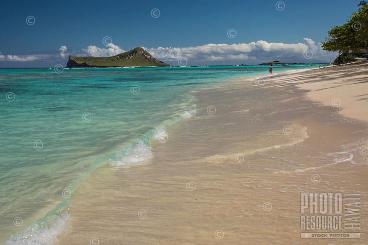 A woman looks out at Manana and Kaohikaipu (or Rabbit and Bird) Islands from Waimanalo Beach, Windward O'ahu.