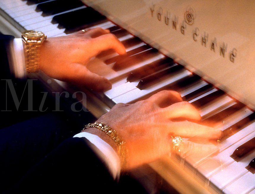 Blurred motion detail image of the hands of a pianist.
