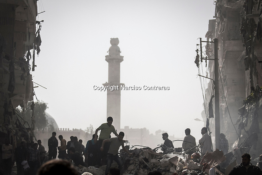 Syrian residents walk through the debris of a destroyed building as they look for bodies after an aistrike hits a residential area in Al-Ansari, a neighborhood under control of the rebel fighters in Aleppo, Syria.