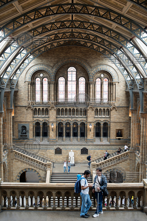 Visitors on a balcony overlooking the Central Hall at Natural History Museum in London.