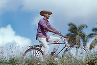June, 1977. Havana, Cuba. Eighteen years after the Cuban Revolution the first U.S. tourists were permitted to visit Havana. Cuban man riding a bicycle, an essential transportation alternative to car, due to oil shortage from Russia.