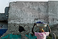 The bullet holes in the wall and the house ruins seen in the slum of Cité Soleil, Port-au-Prince, Haiti, 19 July 2008. There have been a lot of violence and military coups in Haiti in the last years. The overall situation on Haiti gets worse every year and the extreme, hardly imaginable poverty hits more and more people. The Haitian economics is paralysed, there is no infrastructure, no food supplies, the population suffer from hunger, social and living conditions in Haitian slums (e.g. Cité Soleil) are a human tragedy. The rage grows and the tension continues with undiminished strength.