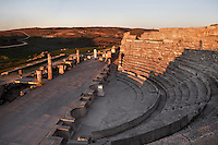 High angle view of Theatre, c. 40-60 AD, Segobriga, Spain, pictured on April 13, 2006, lit by the sunset. Seating 2,000 people, the raked auditorium surrounds a semi-circular stage. The theatre was decorated with ornate columns and statues whose ruins remain. Segobriga was founded by the Romans in the 1st century BC, after the Punic wars, and the town was developed during the reign of  Augustus. It became an important administrative centre whose local industry was mining ëspecularis lapisí, a crystallized sheet gypsum used for window glass. Picture by Manuel Cohen.