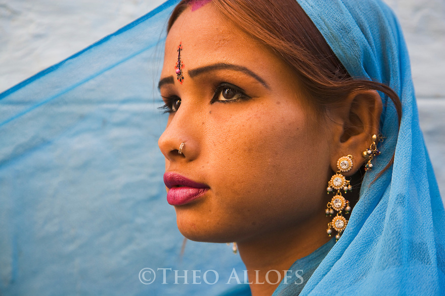 Rajasthani girl in blue dress and traditional Rajasthani jewelry in front of blue house wall in Jaisalmer Fort, Jaisalmer, Rajasthan, India --- Model Released