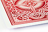 A close up of the red and white patter on the back of a playing card.