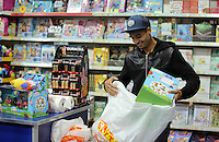 Pictured: Kyle Naughton at the till Wednesday 08 December 2016<br />Re: Swansea City FC players have bought Christmas gifts for 60 children at Smyths toy store in Swansea, south Wales.
