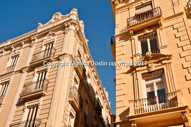 Looking up at balconies on a street corner in Valencia, Spain