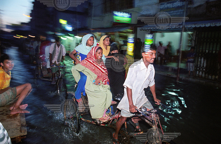 Dhaka is a city of over 600,000 rickshaws. Here, a rickshaw wallah transports four women through flood waters. Monsoon rains caused flooding in 40 of Bangladesh's 64 districts, displacing up to 30 million people and killing several hundred.
