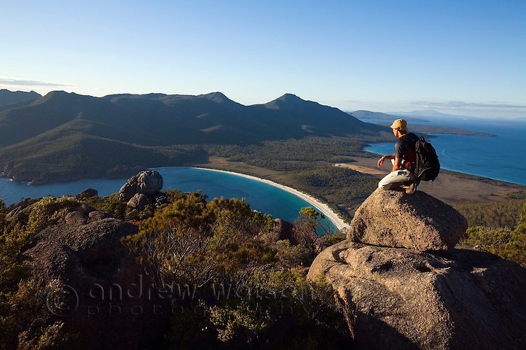 A hiker looks out over Wineglass Bay from atop Mt Amos.  Freycinet National Park, Tasmania, AUSTRALIA
