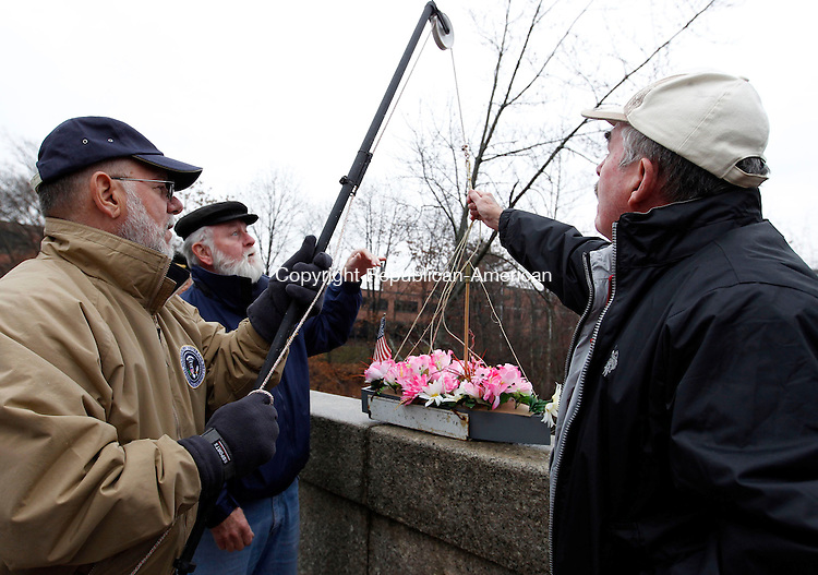 """Waterbury, CT-07 December 2012-120712CM01-  Mike Fox, a U.S Navy Vietnam Veteran, back, Doc Docchio, member of the Waterbury Veterans Memorial Committee, left and Bob Batters of Waterbury, lower the """"USS Never Sailed"""" into the Naugatuck River Friday afternoon in Waterbury.  The trio were apart of a remembrance put on by the Waterbury Veterans Memorial Committee, which honored Pearl Harbor Day by lowering a wreath basket into the Naugatuck River from the Pearl Harbor Memorial Bridge on Freight Street.        The event was apart of the Committee's Pearl Harbor Remembrance Day which also included Patriotic Services, held at the BPOE Elks Club in Waterbury. Christopher Massa Republican-American"""