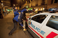 Switzerland. Geneva. Two police officers are frisk searching and arresting a black african man from Guinea who is under the influence of alcohol. Police car. Both policemen are wearing under their jackets a ballistic vest, bulletproof vest or bullet-resistant vest which is an item of personal armor that helps absorb the impact from knives, firearm-fired projectiles and shrapnel from explosions, and is worn on the torso. Soft vests are made from many layers of woven or laminated fibers and can be capable of protecting the wearer from small-caliber handgun and shotgun projectiles. A frisk search (also called a patdown or pat down) is a search of a person's outer clothing wherein a person runs his or her hands along the outer garments to detect any concealed weapons or contraband. 20.03.12 © 2012 Didier Ruef