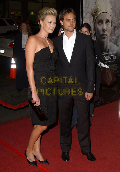 "CHARLIZE THERON & STUART TOWNSEND.Los Angeles Premiere of ""North Country"" held at The Grauman's Chinese Theatre in Hollywood, California  .October 10th, 2005.RefL DVS.full length black strapless dress celebrity couple boyfriend girlfriend black suit.www.capitalpictures.com.sales@capitalpictures.com.Supplied By Capital PIctures"