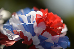 Merrick, New York, U.S. - May 26, 2014 - Detail of a red white and blue cloth flower decorating a memorial wreath at The Merrick Memorial Day Parade and Ceremony, hosted by American Legion Post 1282 of Merrick, honoring those who died in war while serving in the United States military.