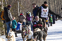 Justin Savidis and team run past spectators on the bike/ski trail during the Anchorage ceremonial start during the 2014 Iditarod race.<br /> Photo by Britt Coon/IditarodPhotos.com