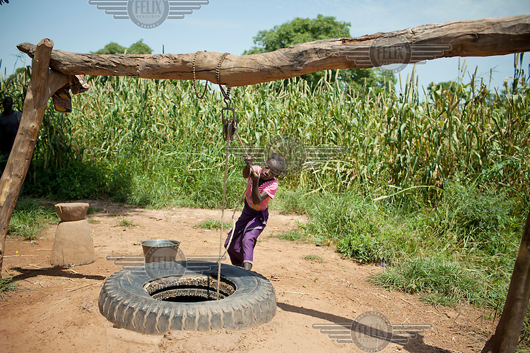 Awa Sanogo hauls up water from a well outside her home. /Felix Features