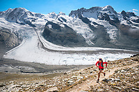 A woman trail running above Zermatt, Switzerland with the Monte Rosa in the background.