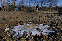 Ice covers a depression in the ground as volunteers clear honeysuckle and other invasive plants from Otterbein Lake in Westerville, Ohio, on a cold winter morning. The once abandoned lake was used as a holding pond for industry.  Photo Copyright Gary Gardiner. Not for reproduction without written permission.