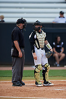 UCF Knights catcher Jordan Rathbone (34) talks with home plate umpire John Bennett during a game against the Siena Saints on February 17, 2019 at John Euliano Park in Orlando, Florida.  UCF defeated Siena 7-1.  (Mike Janes/Four Seam Images)