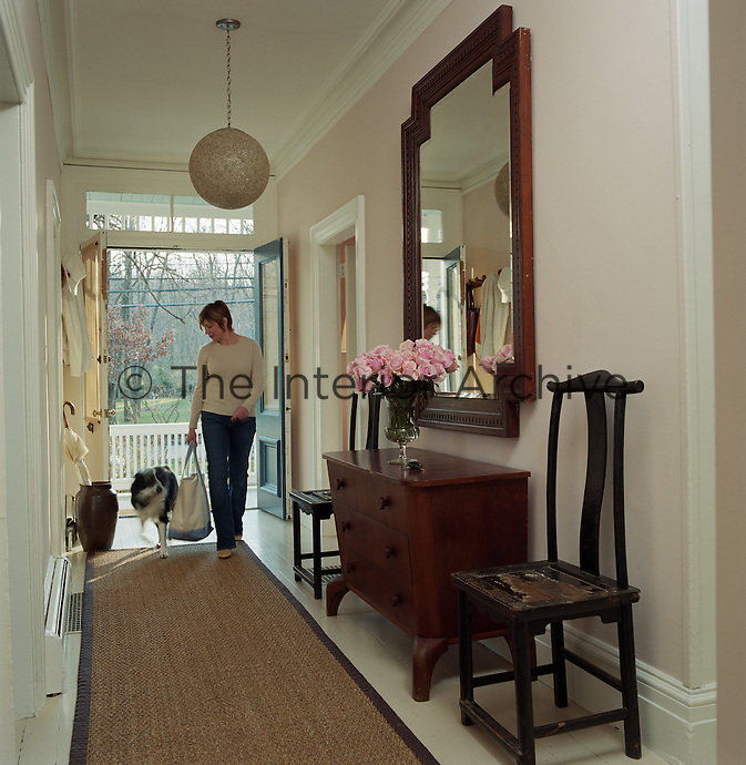 Portrait of interior designer Sharon Simonaire walking into her house with her dog